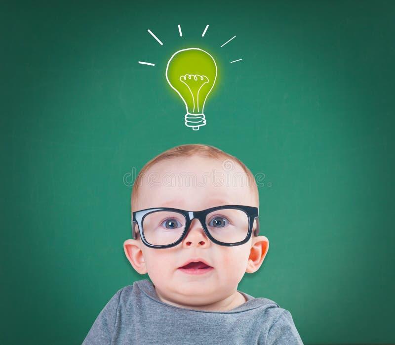 戴眼镜的婴孩有一个想法 免版税库存图片