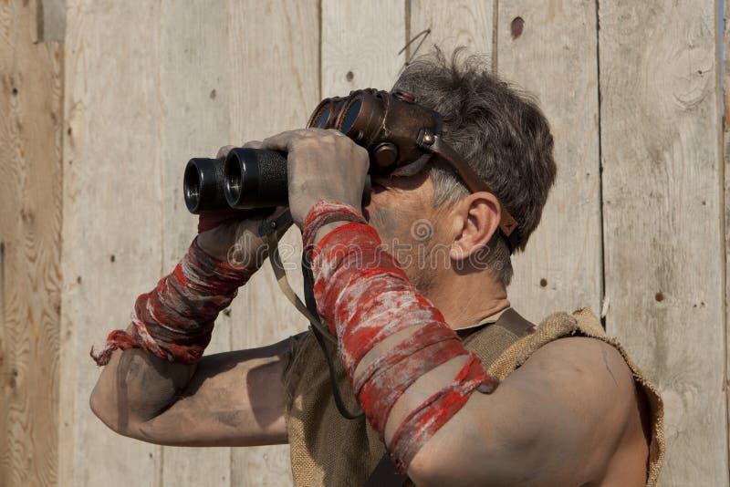 戴眼镜的Steampunk人通过看双筒望远镜 图库摄影