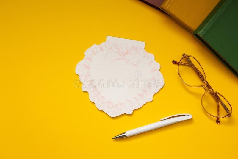 眼镜,书,关于黄色背景的笔记 库存图片