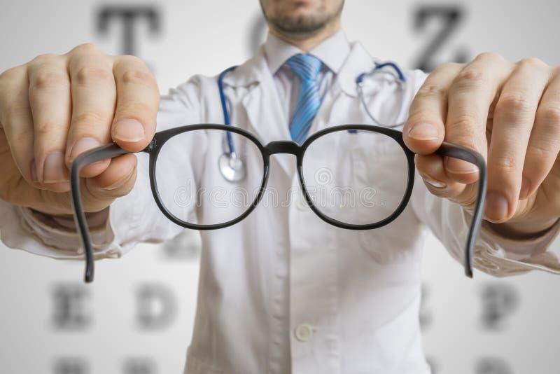 眼医医生为患者提供玻璃 眼睛视域测试概念 库存图片