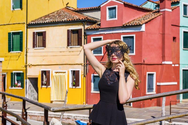 戴着一个黑面具的女孩在Burano海岛,意大利 库存照片