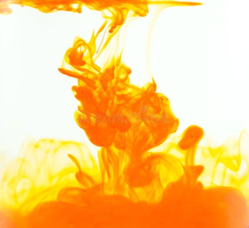 着墨下落,橙色颜色下落在水中 墨水云彩在水中在白色背景 免版税库存图片