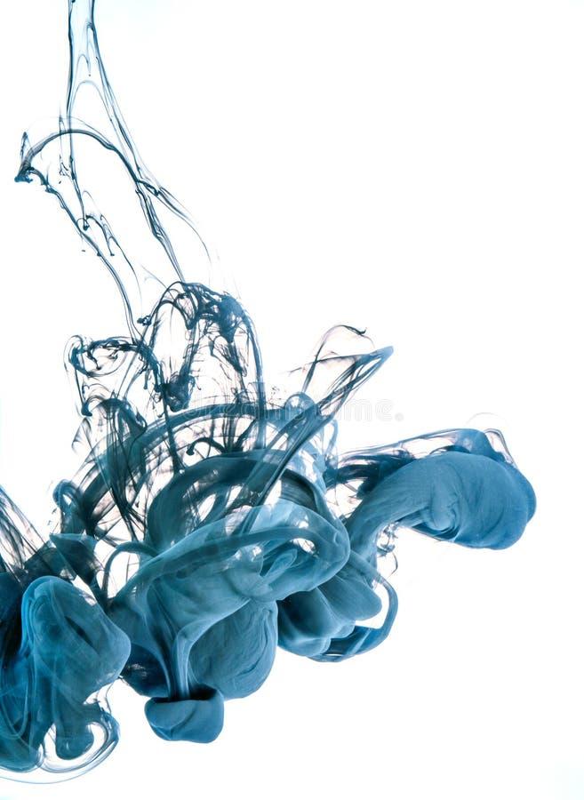着墨漩涡在白色背景的水中 油漆在水中 软的传播小滴色的墨水在水中 库存照片