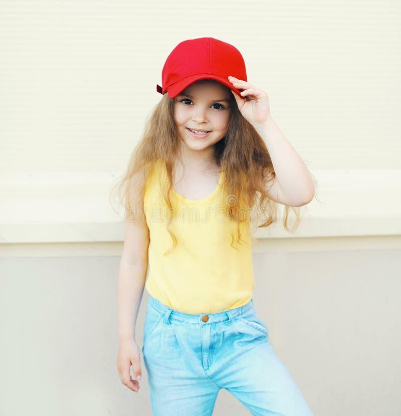 戴着帽子的时髦的矮小的逗人喜爱的女孩孩子 免版税库存照片