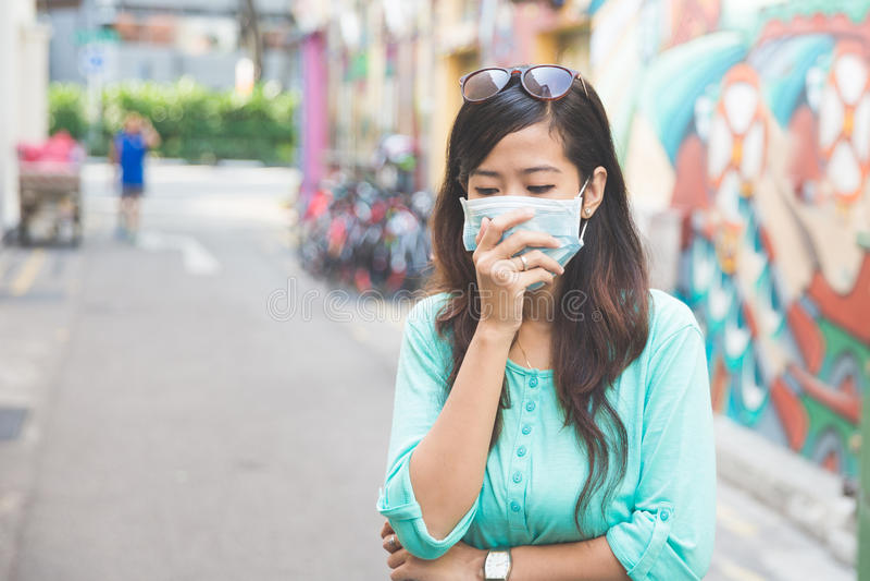 戴着医疗面罩的妇女在城市 库存照片