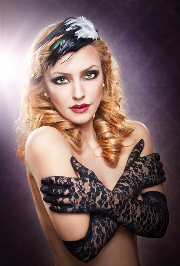 戴着黑鞋带手套的一名露胸部的白肤金发的妇女的特写镜头画象 图库摄影