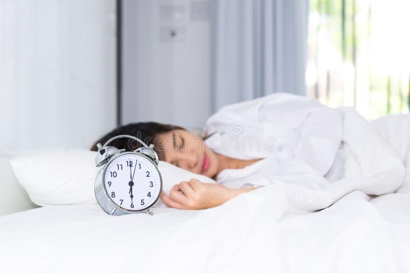 睡眠妇女与闹钟的早晨 免版税库存图片