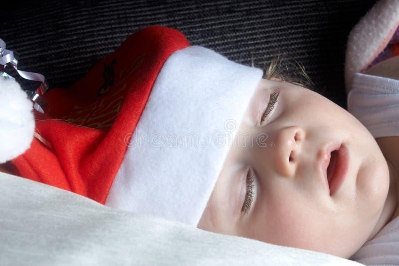 睡着的子项戴圣诞节帽子 免版税库存照片