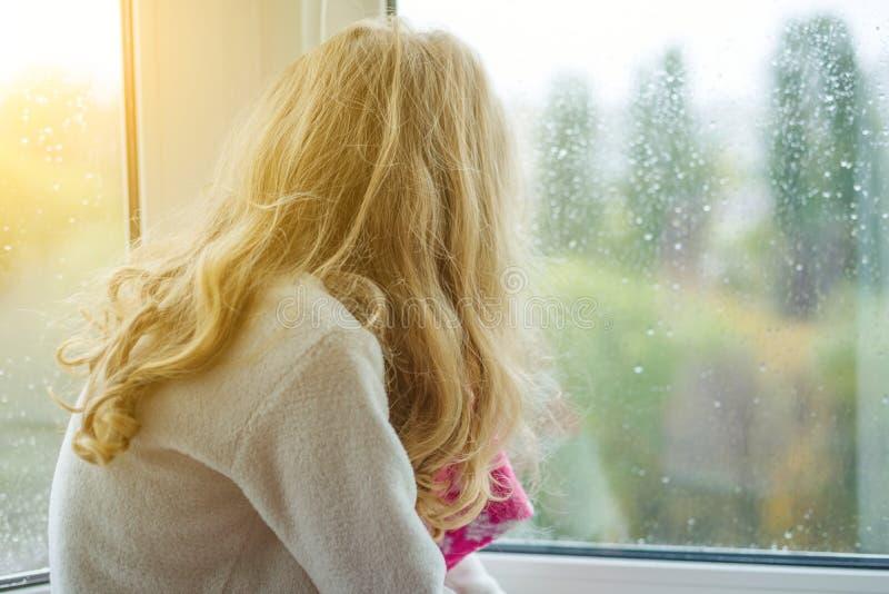 睡衣的一个孩子在与雨下落的秋天窗口里微笑 库存照片
