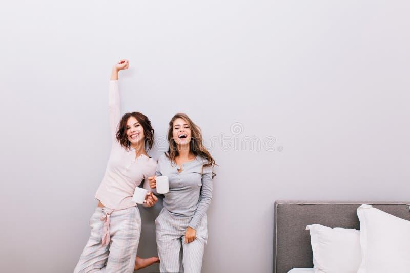 睡衣的两个年轻俏丽的女孩有杯子的在灰色墙壁背景的睡房 获得乐趣和微笑的他们 免版税库存照片