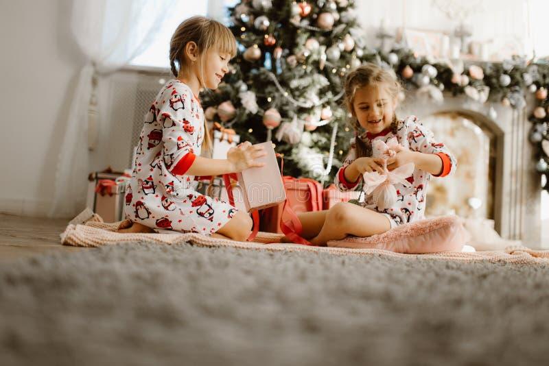 睡衣的两个愉快的妹坐地毯并且打开新年的礼物在有美丽的轻的舒适屋子 免版税库存图片