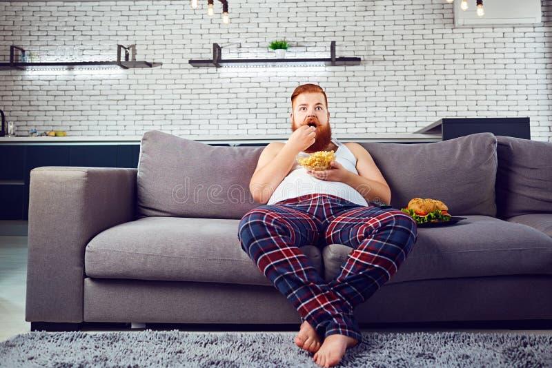 睡衣的厚实的滑稽的人吃汉堡的坐长沙发 免版税库存图片