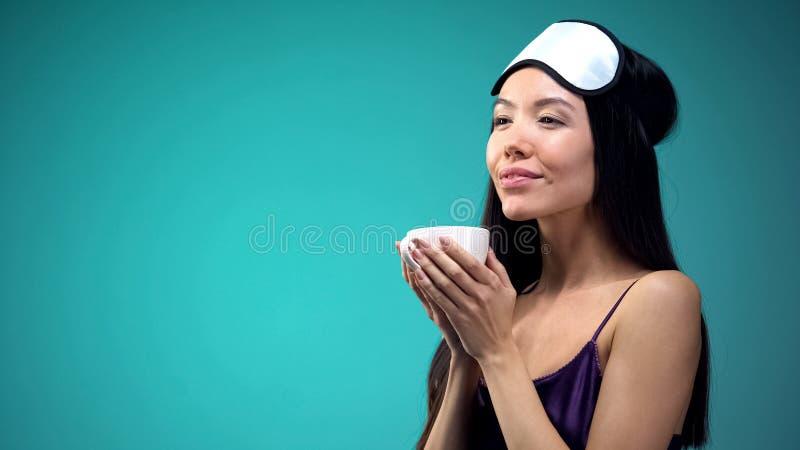睡衣的可爱的女孩享受安慰的清凉茶芳香在睡觉前 免版税库存图片