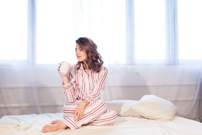 睡衣的女孩早晨醒了和饮料咖啡或者茶 库存图片