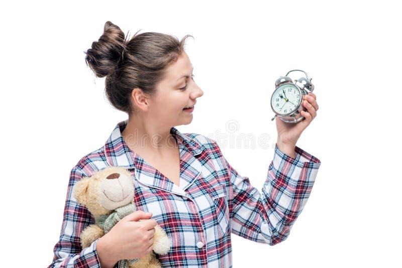 睡衣的女孩看闹钟并且在手中拿着女用连杉衬裤 免版税库存图片