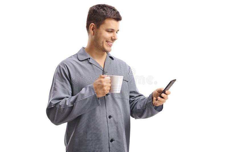 睡衣的年轻人有电话和杯子的 库存图片