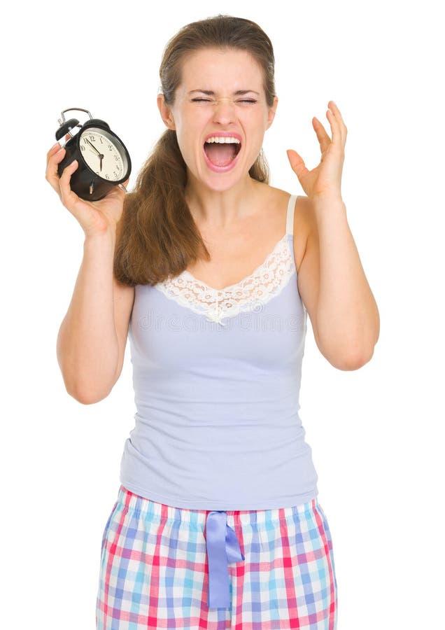 睡衣的强调的妇女有敲响的闹钟的 图库摄影