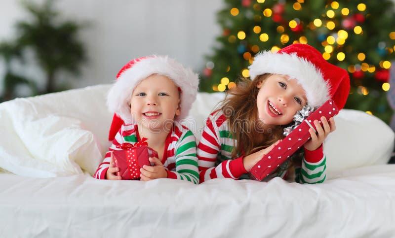 睡衣的愉快的孩子有近礼物的在圣诞节早晨 免版税库存照片
