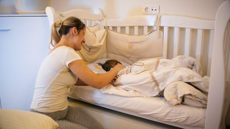 睡衣的美丽的年轻母亲爱抚她逗人喜爱的小孩儿子的睡觉在小儿床在托儿所 免版税图库摄影