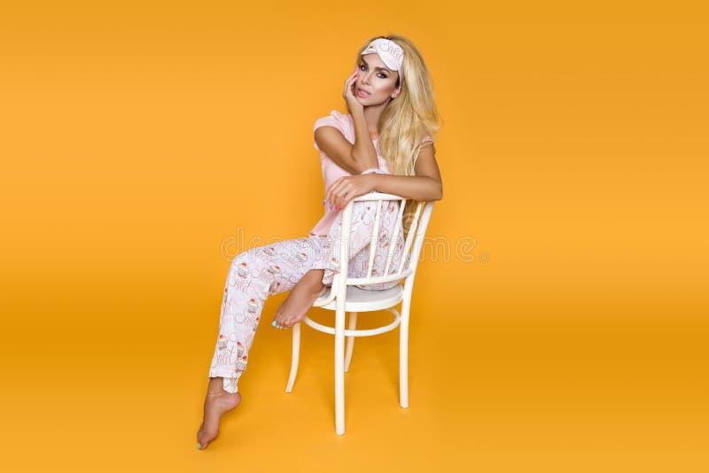 睡衣的美丽的白肤金发的妇女在黄色背景在演播室 免版税图库摄影
