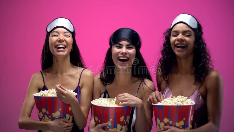 睡衣的观看滑稽的喜剧用玉米花的笑的妇女和眼罩 免版税库存图片
