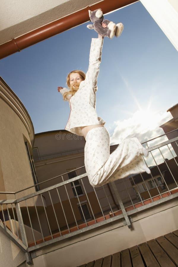 睡衣的运动的妇女在阳台 免版税库存照片