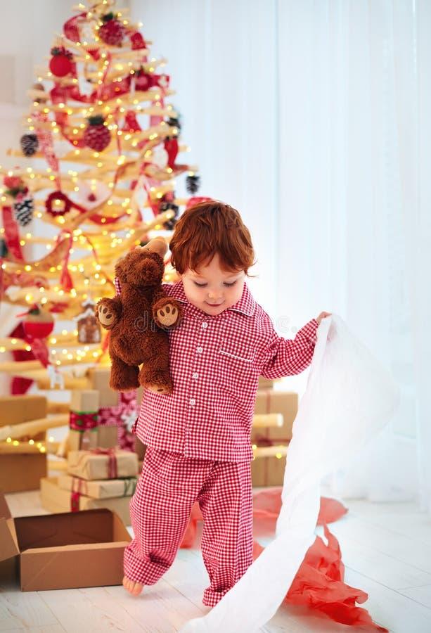 睡衣的逗人喜爱的愉快的小孩男孩有他的在圣诞节的礼物 免版税库存照片