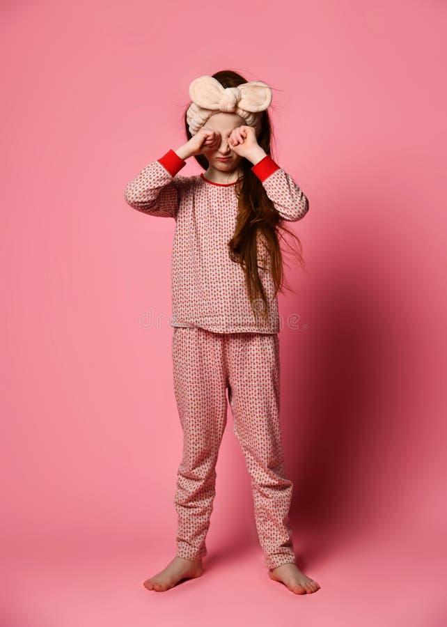 睡衣的逗人喜爱的红发女孩叫醒了并且摩擦了她的眼睛 库存图片