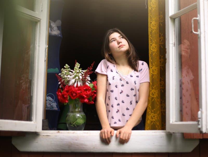 睡衣神色的欧洲青少年的女孩在窗口外面早晨 免版税图库摄影