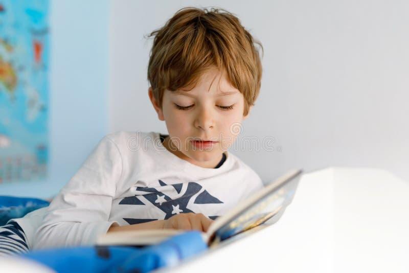 睡衣阅读书的逗人喜爱的白肤金发的小孩男孩在他的卧室 大声读激动的孩子,坐在他的床上 免版税库存照片