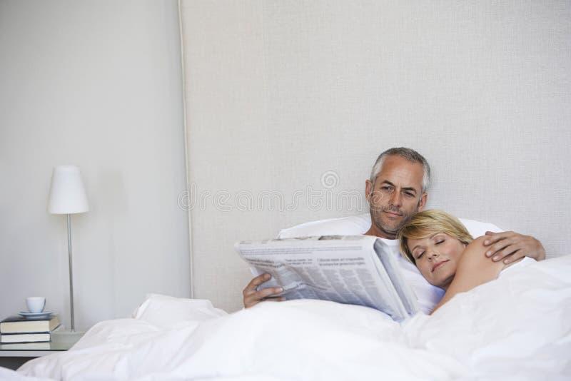 睡觉与人读书报纸的妇女在床上 免版税库存图片