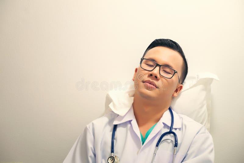 睡觉与在医院诊所的听诊器的劳累过度的医生 免版税库存照片