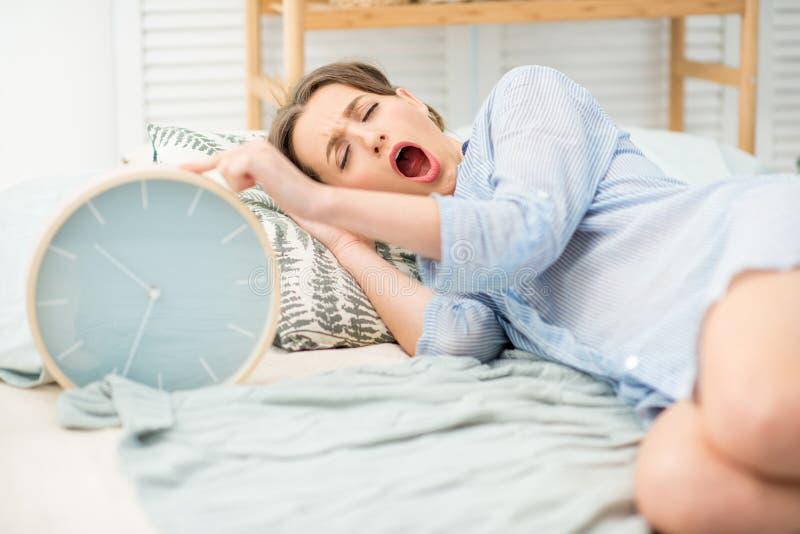 睡觉与在床上的时钟的妇女 免版税库存图片