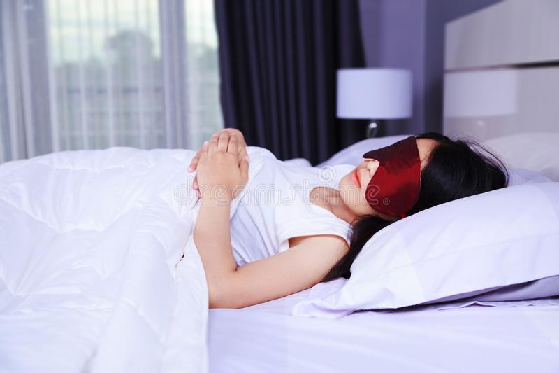 睡觉与在床上的眼罩的妇女 免版税库存图片