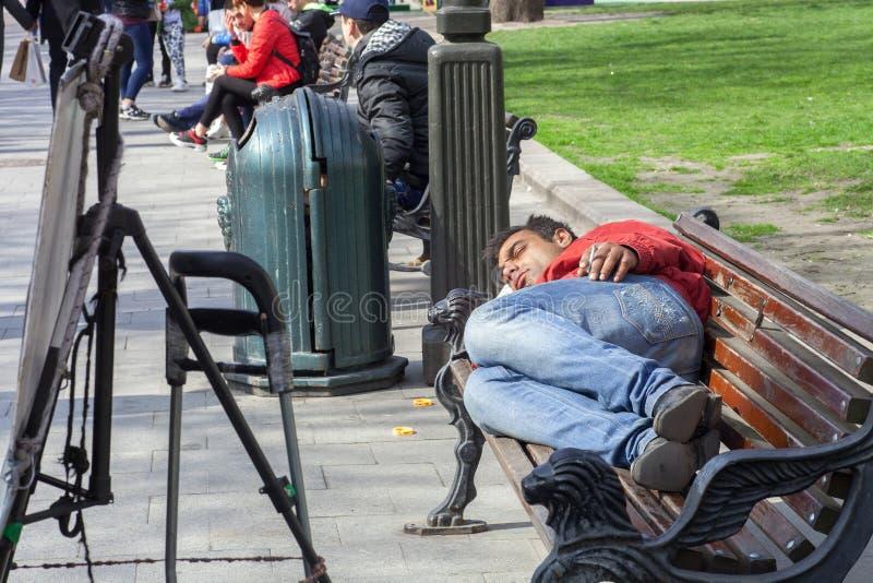 睡觉与在长凳的香烟的无家可归的人在街道上 免版税图库摄影