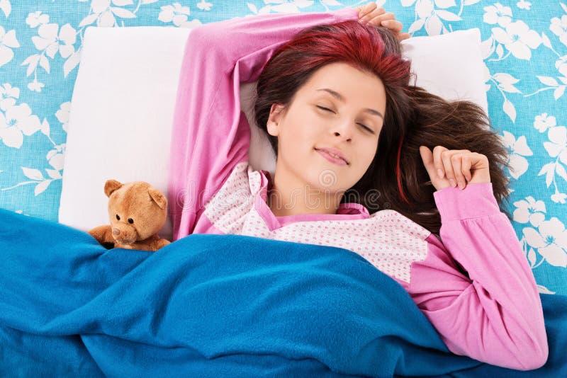 睡觉与她的玩具熊的女孩 免版税库存照片