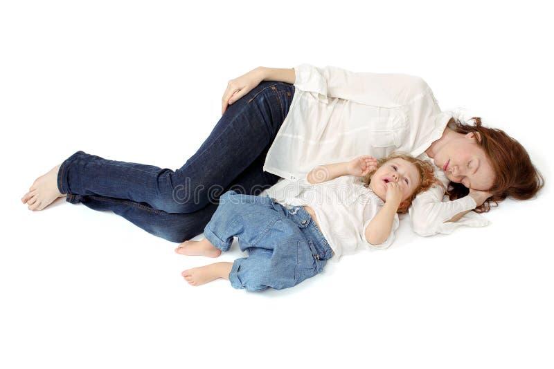 睡觉与她醒的孩子的妈妈 免版税库存图片