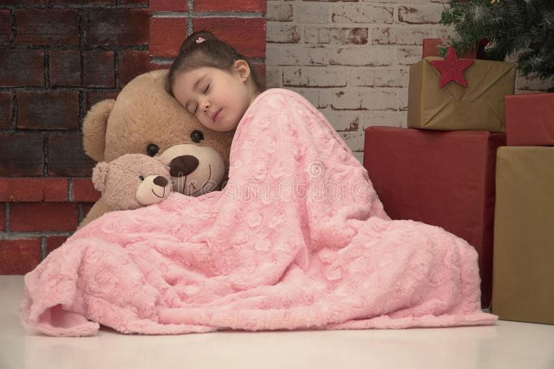 睡觉与巨大的长毛绒的小女孩涉及等待圣诞老人的地板 免版税库存照片