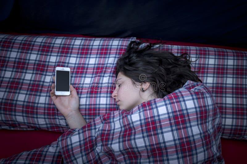睡觉与智能手机 免版税库存图片