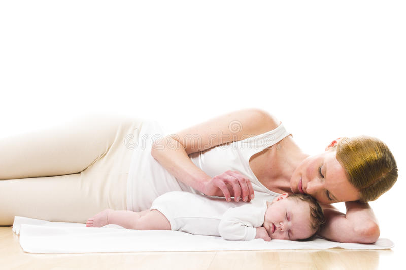 睡觉与母亲的新出生的婴孩 免版税库存图片