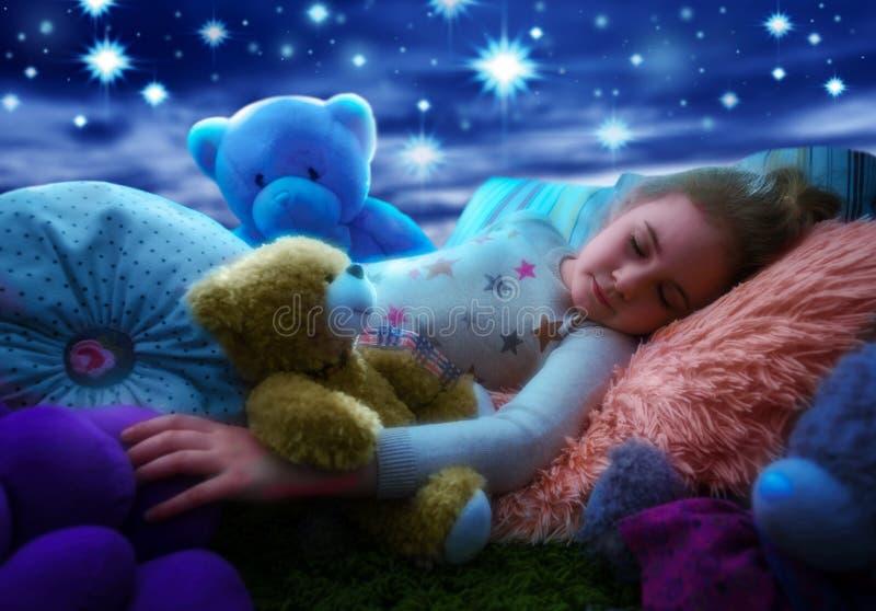 睡觉与玩具熊的小女孩在床上,作满天星斗的天空在上床时间晚上 免版税库存图片