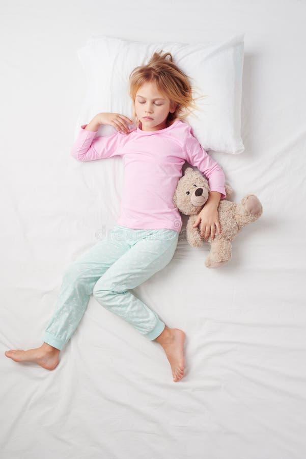 睡觉与玩具熊的小女孩顶视图 库存图片
