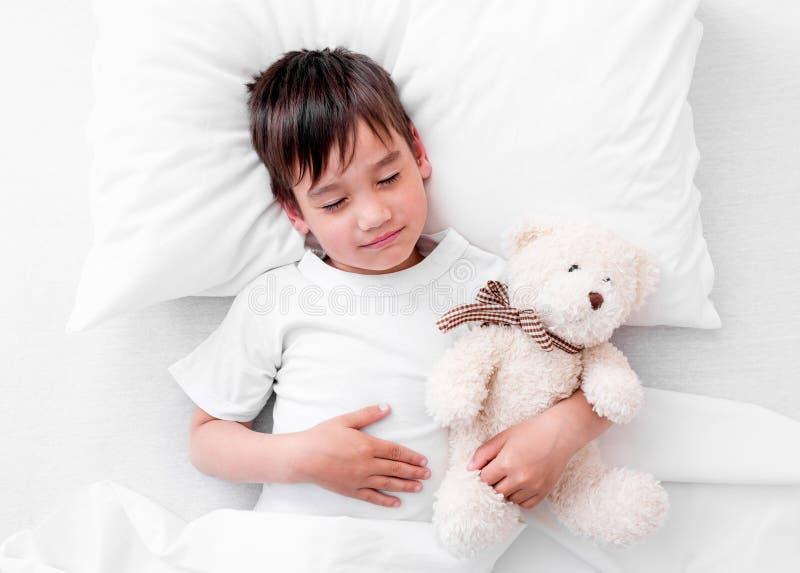 睡觉与玩具熊的小孩男孩 库存图片