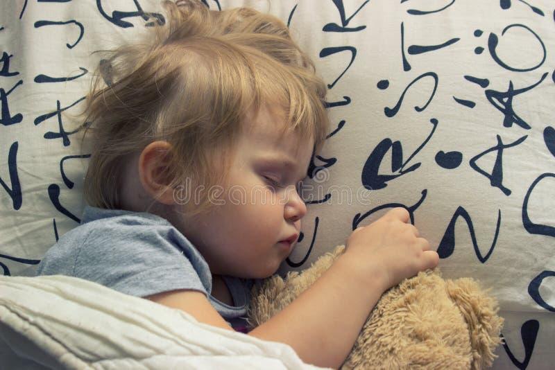 睡觉与玩具熊的小孩 免版税库存图片