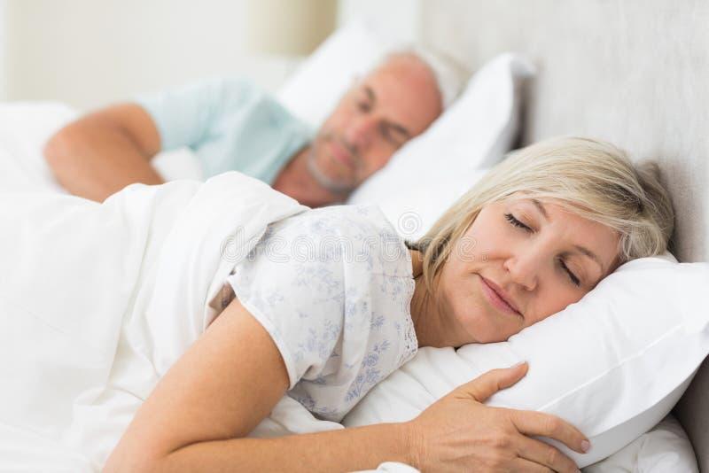 睡觉与眼睛的成熟夫妇在床上关闭了 免版税库存图片