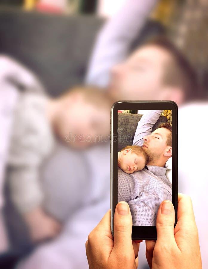 睡觉与逗人喜爱的睡觉的新生儿的年轻父亲说谎在他的与下来胳膊的胸口 母亲提供场面与sm 库存照片