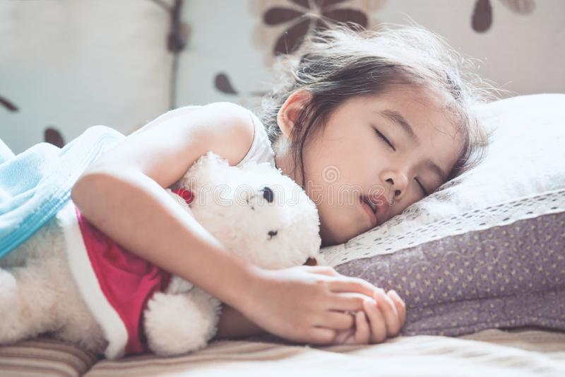 睡觉和拥抱她的玩具熊的逗人喜爱的亚裔儿童女孩 免版税库存图片