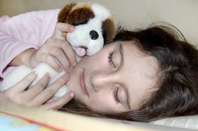 睡觉和拥抱她的玩具的小女孩 免版税图库摄影