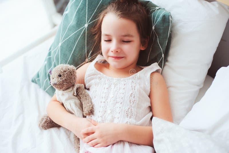 睡觉和观看与她的玩具熊的逗人喜爱的小孩女孩美梦 免版税库存照片