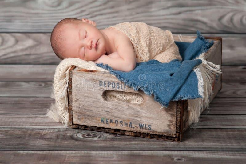 睡觉在一个木板箱的新出生的男婴 免版税库存照片